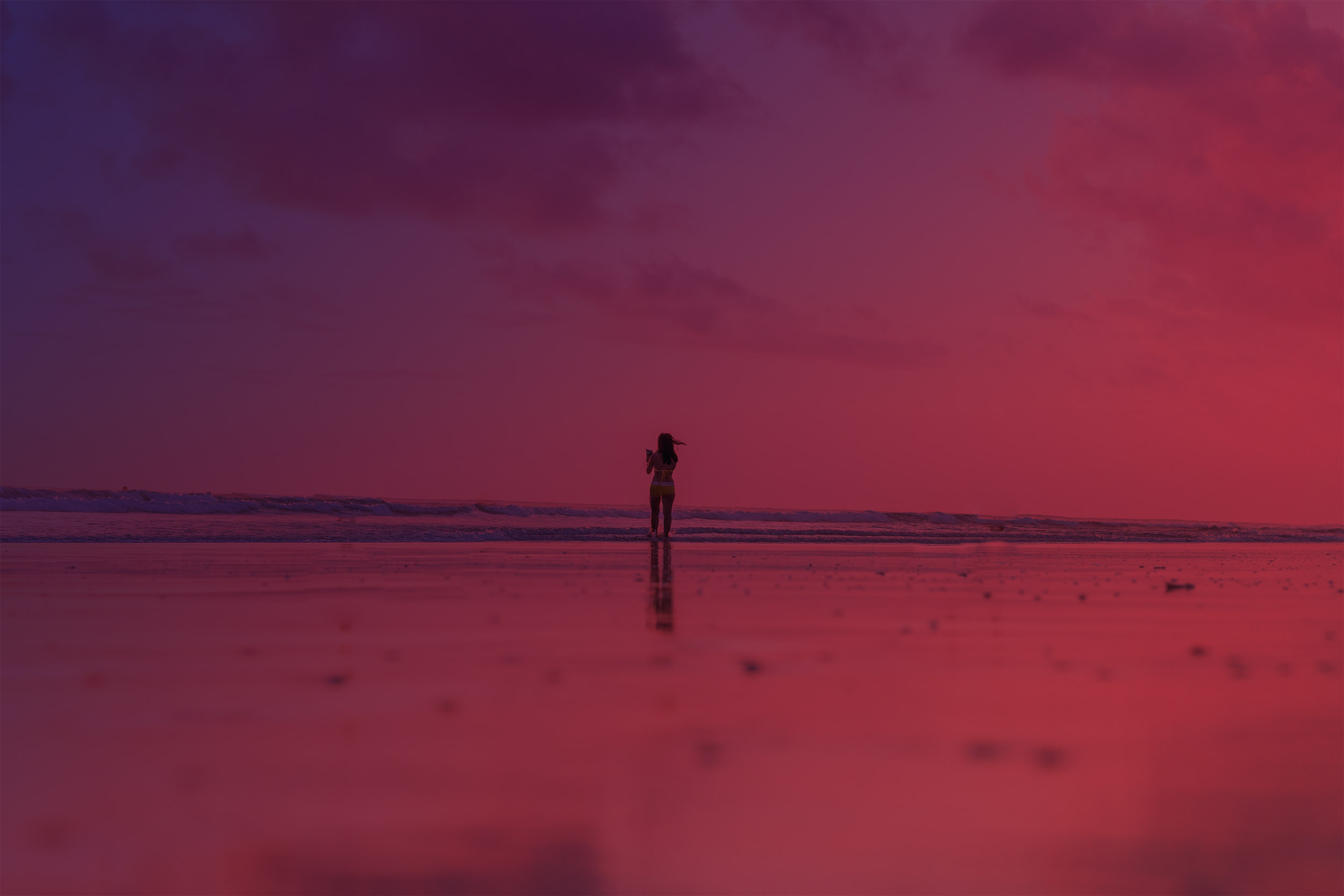 Girl standing on beach overlooking the ocean
