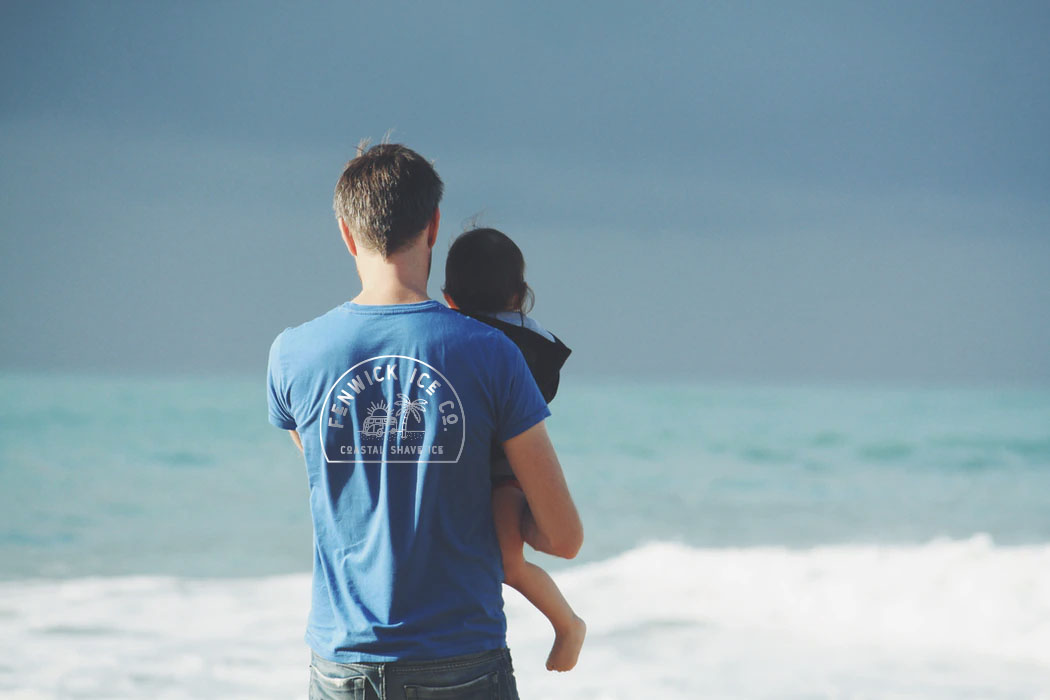 father and daughter on beach wearing fenwick ice t-shirt